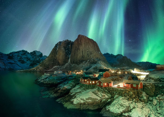 Sea by mountain against aurora borealis