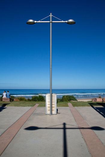 Street light by sea against clear blue sky