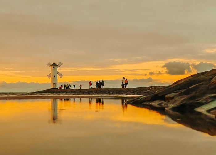 Reflection of people on water at sunset