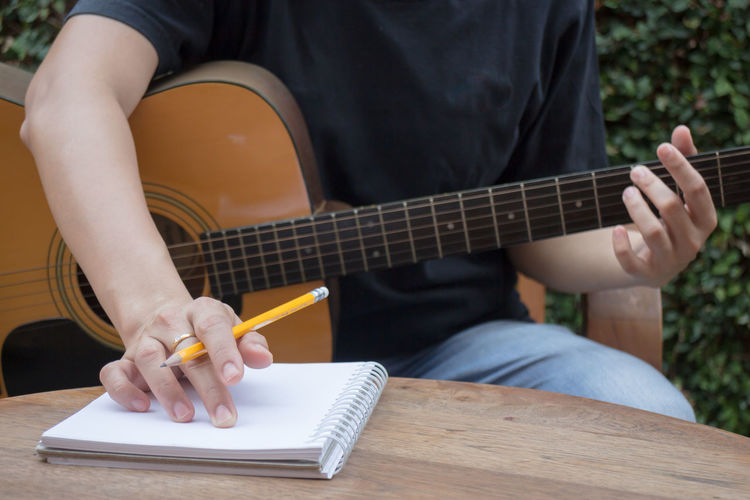 Midsection of men writing on diary while playing guitar