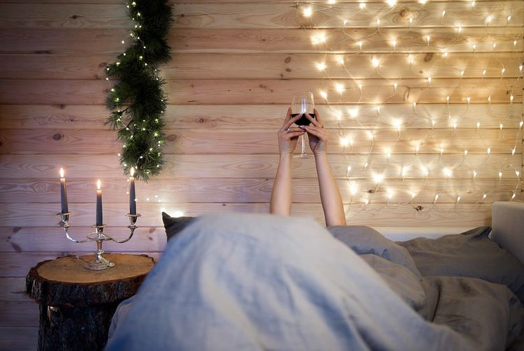 woman relaxing Woman People Hands Wine Glass Rest Relax Relaxing Moments Bed Bedroom Candles Light Cabin Rustic Wooden Mountain Cabin Christmas Decoration Lighting Equipment Burning Celebration Holiday Illuminated Winter