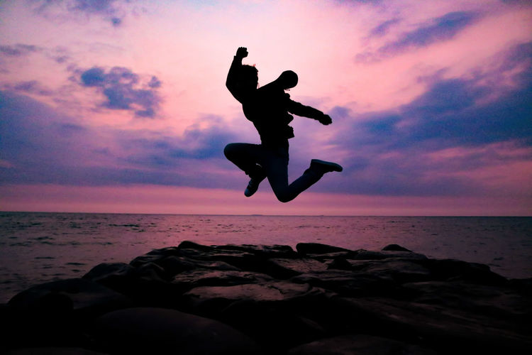 Silhouette man jumping on rock at beach during sunset