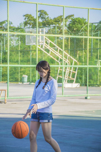 Cute girl playing basketball Sport Basketball - Sport Ball One Person Playing Basketball - Ball Court Leisure Activity Child Competition Three Quarter Length Basketball Player Athlete Net - Sports Equipment Day Clothing Fence Standing Teenager Basketball Uniform