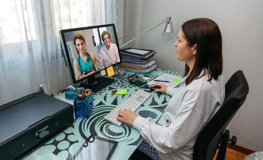 Doctor video conferencing witth collegues over computer
