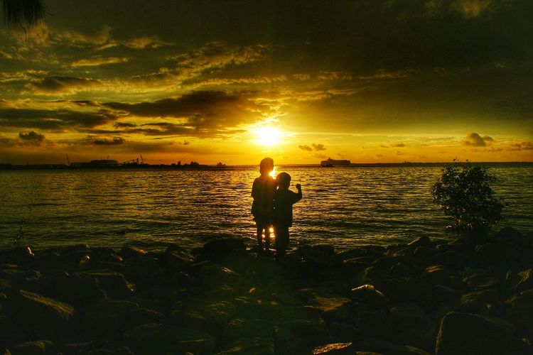 Two kids silhoutte watching sunset Sunset Silhouettes Kids Yellow Klang Sunset Sea One Person Silhouette People Water Summer Beach Nature 2018 In One Photograph