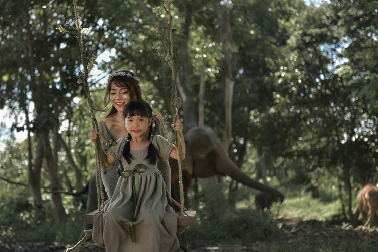 Portrait of happy girl sitting on swing with mother standing against elephant
