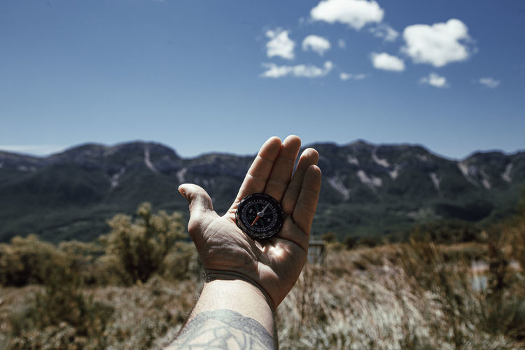 Man's hand holding a compass to orient himself on the mountain person