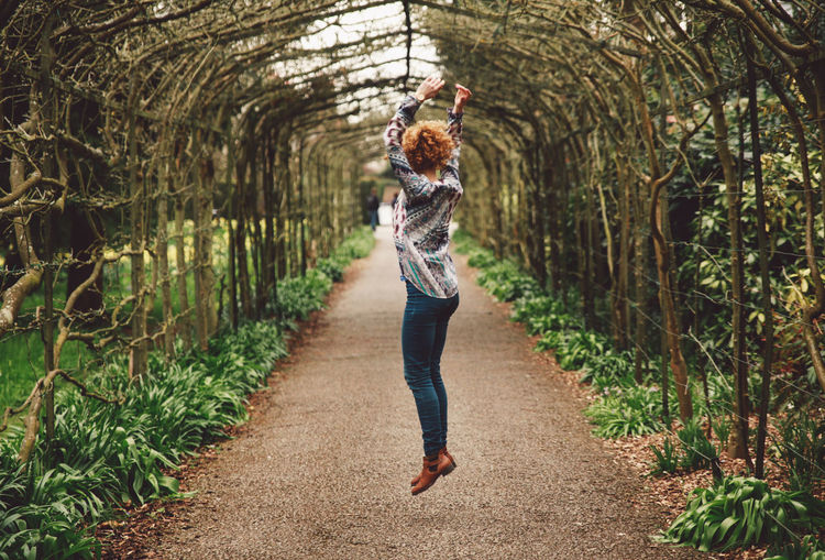 Woman Jumping On Footpath Covered With Plants At Park