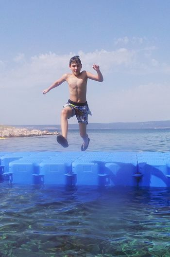 Jump Beauty In Nature Boy Childhood Day Front View Full Length Fun Horizon Over Water Jumping Leisure Activity Lifestyles Mid-air Nature One Person Outdoors Real People Sea Sea And Sky Shirtless Sky Vacations Water Connected By Travel Be Brave