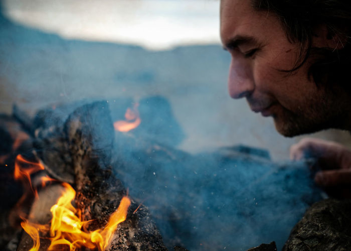 Close-up of man burning campfire outdoors