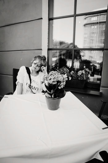 Woman sitting by potted plant on table in restaurant