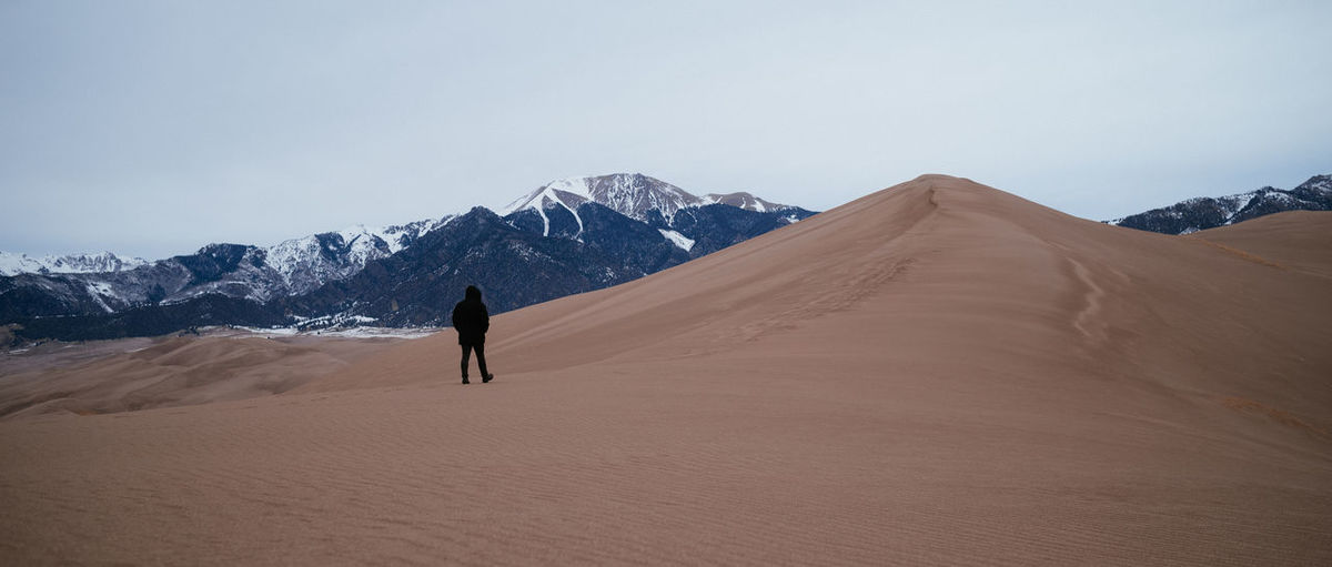 Full length of man walking on arid landscape against mountains and sky