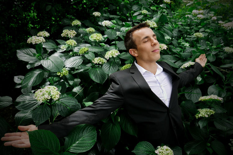 Businessman with arms outstretched standing amidst plants