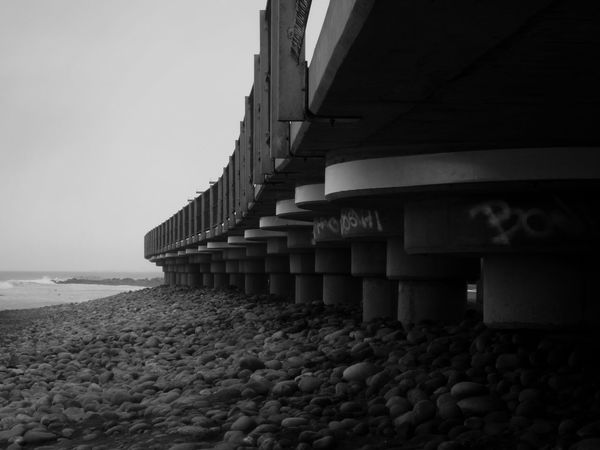 (Miraflores, may 2017) Beach Sand Sea Pebble Architecture Day No People Built Structure Nature Water Outdoors Horizon Over Water Sky Monochrome Wave Sea And Sky Miraflores Fine Art Photography Lima Concret Bridge Horizon Blackandwhite Photography Vacations Autumn The Great Outdoors - 2017 EyeEm Awards