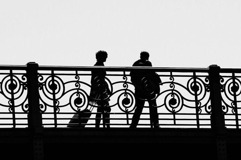 Silhouette men on railing against clear sky
