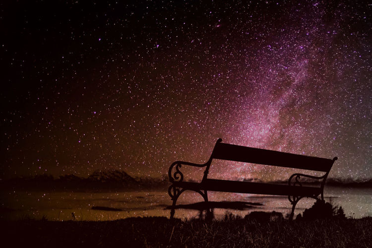 Low angle view of bench on the top of a mountain against a beatiful sky at night. time to think