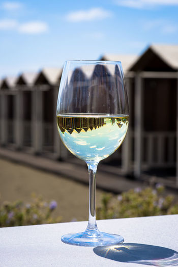 Close-up of wine with reflection in glass on table during sunny day
