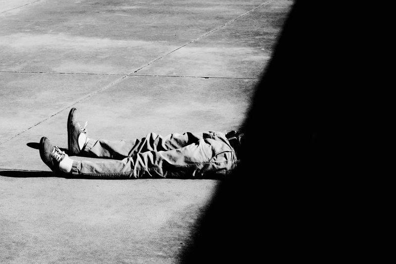 Low Section Of Man Lying On Footpath