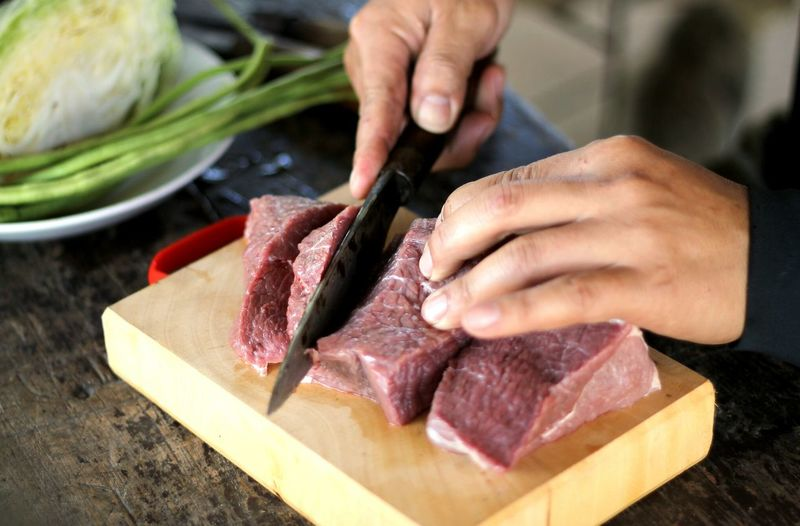 Cropped image of chef cutting meat at kitchen counter