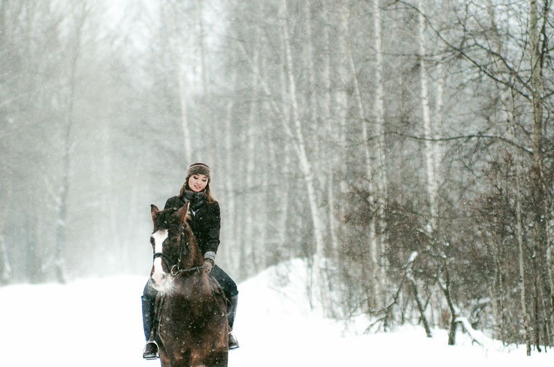 Beautiful Woman Riding Horse On Snow Covered Field