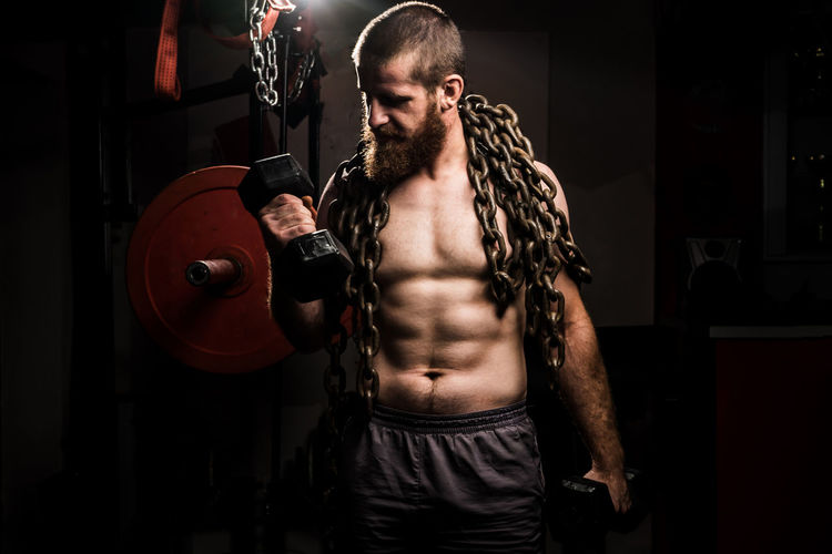 Strength Muscular Build One Person Exercising Lifestyles Sport Indoors  Sports Training Healthy Lifestyle Front View Standing Adult Weight Athlete Weights Shirtless Tattoo Men Vitality Weight Training  Effort