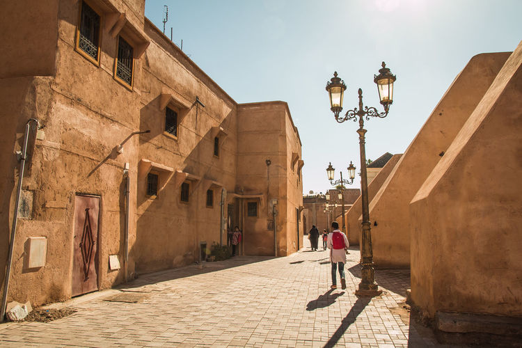 Traditional alleyways in the medina of marrakesh morocco. Marrakesh Nights Morocco Alley Architecture Building Building Exterior Built Structure Day Electric Lamp History Lifestyles Lighting Equipment Marrakech Nature One Person Outdoors Real People Shadow Sky Street Street Light Sunlight The Past Walking Women