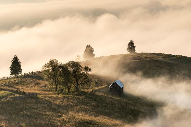 Hut on mountain against sky