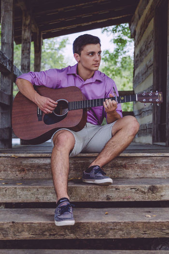 Attractive Brown Eyes Cabin Casual Clothing Dark Hair Day Full Length Guitar Handsome Looking Away Male Man Person Portrait Purple Shirt Rustic Shorts Sitting Stairs Young Adult