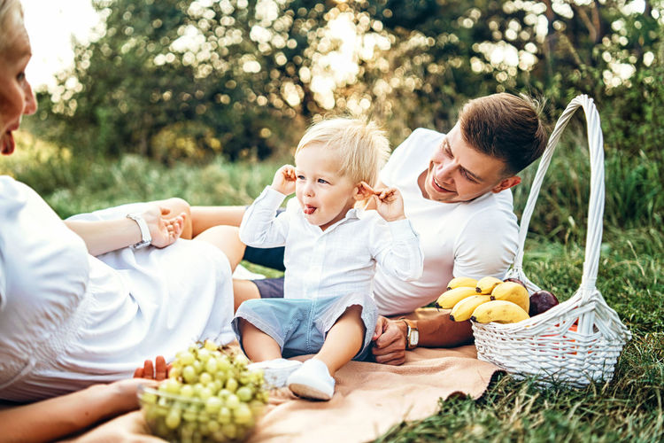 Happy family have fun outdoor Childhood Child Togetherness Men Males  Family Boys Parent Son Positive Emotion Picnic Food Outdoors Basket Fruits Mother Father Family Love  Family Values Nature Park Having Fun Happiness