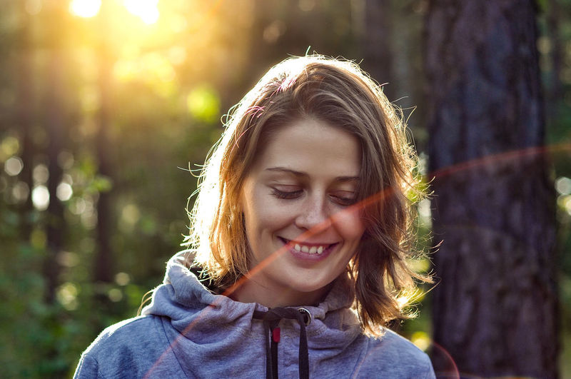 Beautiful Woman Brown Hair Day Emotion Focus On Foreground Front View Hair Hairstyle Happiness Headshot Leisure Activity Lifestyles Nature One Person Outdoors Portrait Real People Smiling Sunlight Tree Women Young Adult Young Women