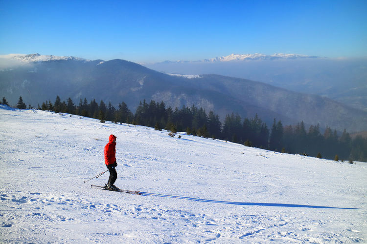 Side view of person skiing on snow covered slope against mountains