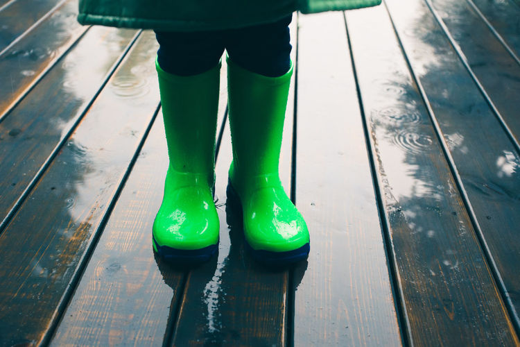 Low section of person wearing rubber boots while standing on wet boardwalk