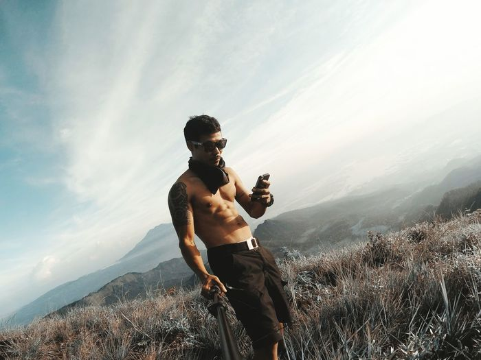 Shirtless mid adult man using mobile phone while standing on mountain against sky