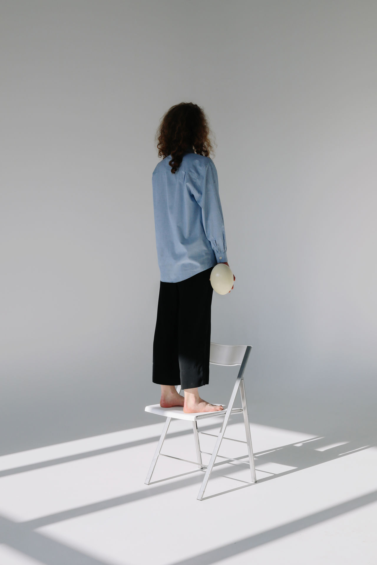 Rear view of woman standing on chair against wall