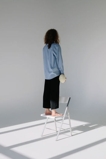 Full Length One Person Women Standing Rear View Studio Shot Gray Background Hairstyle Young Adult Indoors  Casual Clothing Wall - Building Feature Copy Space Real People Facing Away Girls Girl Females Female Chair Minimalism Minimalist Curly Hair Curls Egg Casual Look Casual Holding Standing Fashion Light And Shadow