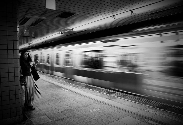 Woman By Blurred Motion Of Train At Railroad Station Platform
