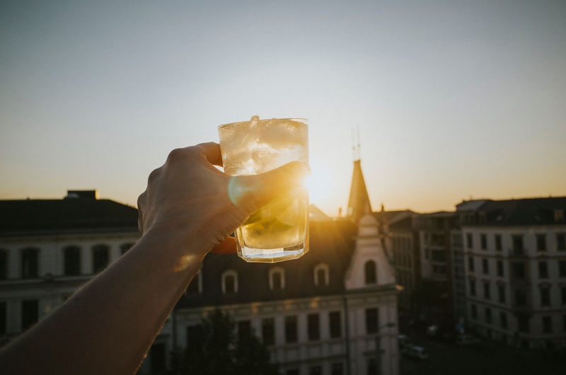 Cropped Image Of Hand Holding Drink Against Buildings During Sunset