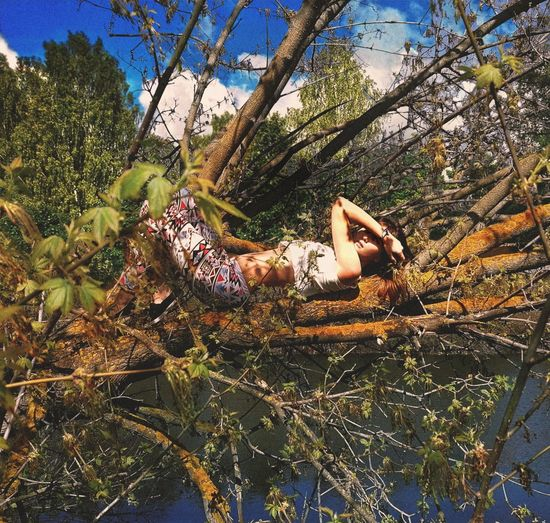 Side view of woman relaxing on tree