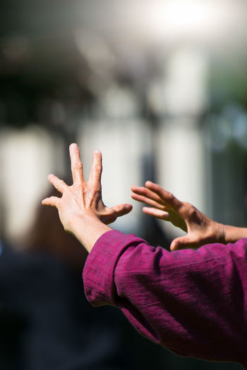 Cropped hand of woman gesturing against blurred background