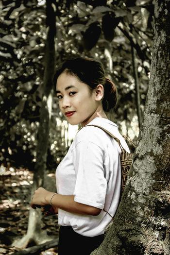 Portrait of woman standing on tree trunk
