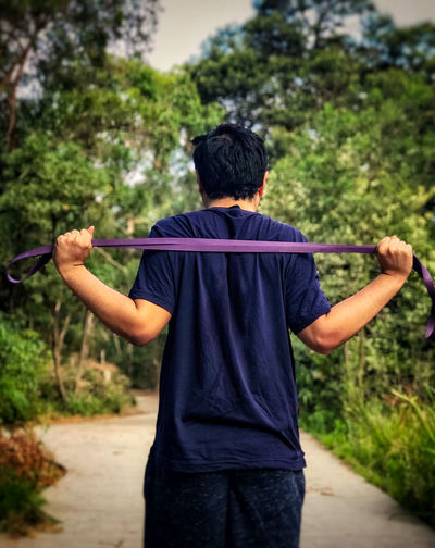 Rear view of man doing resistance band exercises against trees.