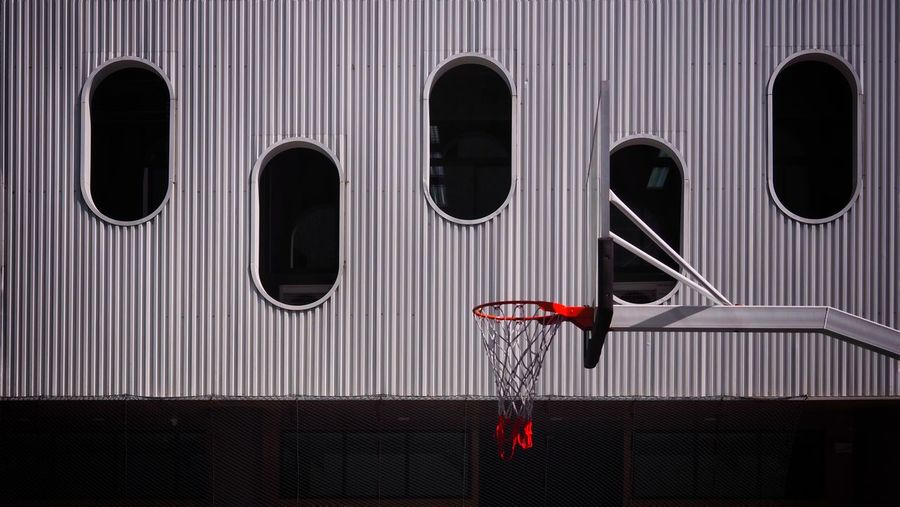 Basketball hoop with contemporary design architecture background contrast.