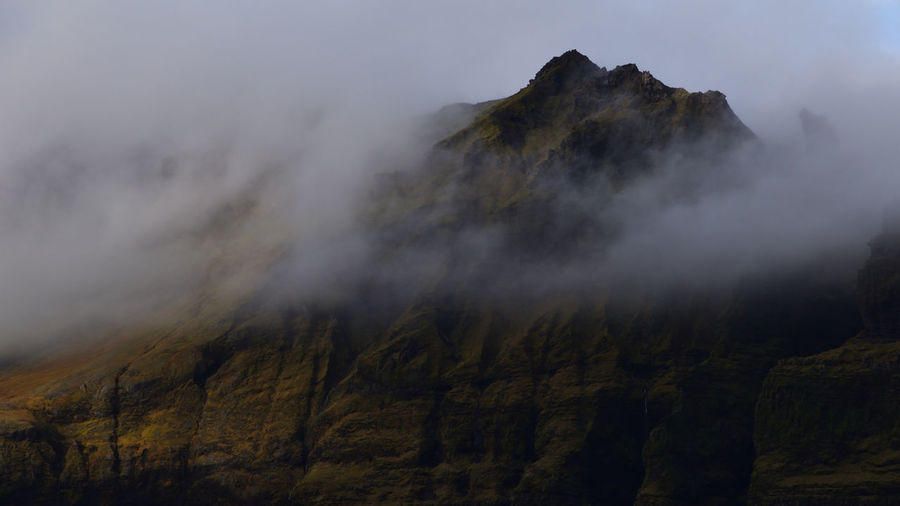 View of mountain amidst fog during winter