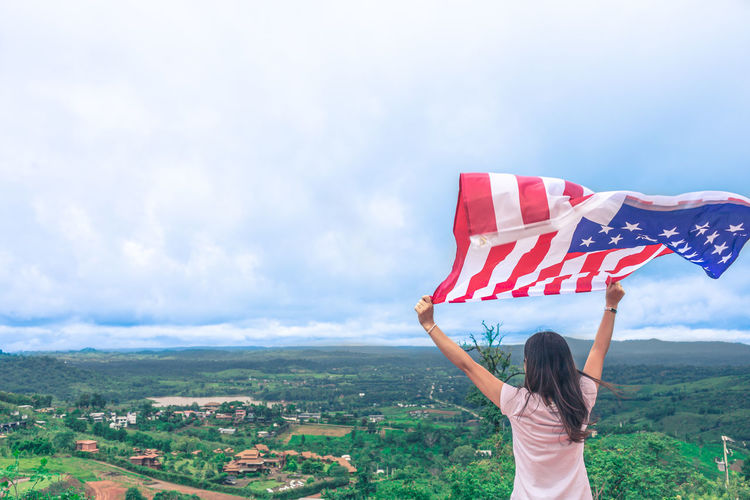 Rear view of woman holding flag against sky