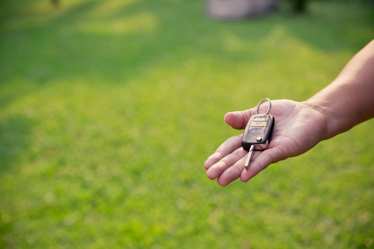 Cropped hand of person holding car key on field