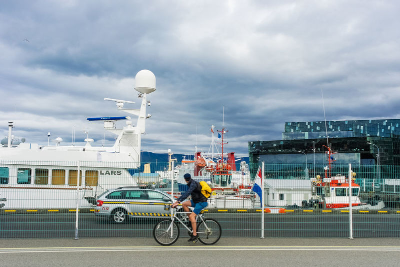 A man is riding a bicycle in the port of Reykjavik. Harbor Iceland Reykjavik Architecture Bicycle Building Exterior Built Structure City Cloud - Sky Day Editorial  Full Length Land Vehicle Lifestyles Men Mode Of Transport One Person Outdoors People Real People Riding Sky Transportation