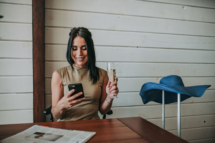 Woman using mobile phone while having wine at home