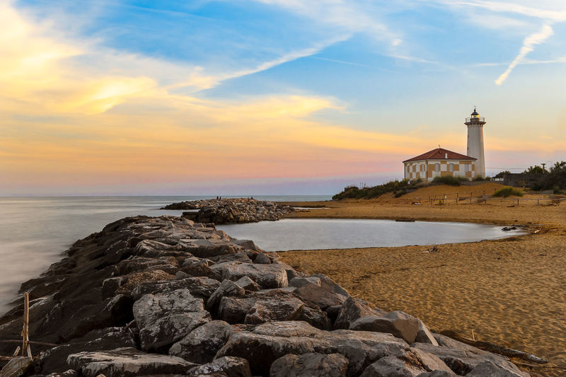 Bibione Light House Water Sea Sky Built Structure Architecture Building Exterior Tower Sunset Lighthouse Beach Land Cloud - Sky Rock Scenics - Nature Nature Building Solid Rock - Object Guidance No People Horizon Over Water Outdoors Cliff Cliffs Cliffside