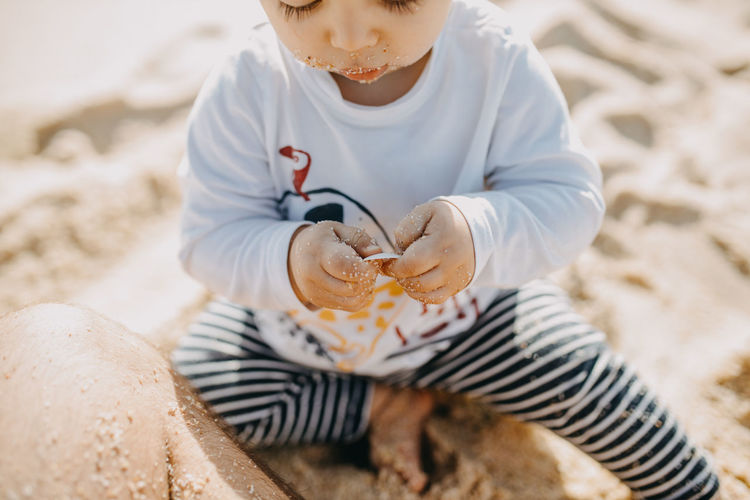 High angle view of boy sitting on beach