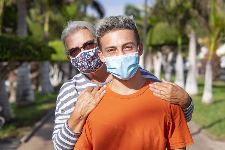 Portrait of grandmother and grandson wearing mask standing outdoors